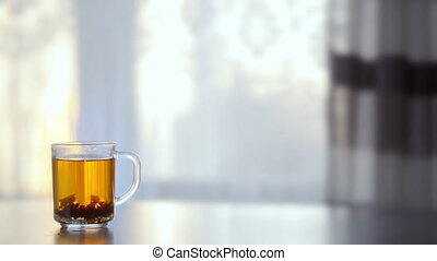 a Cup of steaming hot tea on the table against the window.