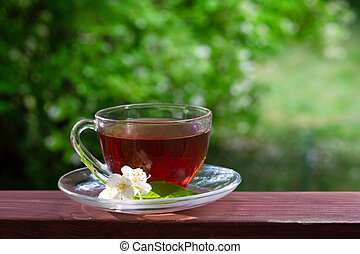 A cup of tea, a number of jasmine flowers. Green blurred background with white flowers. Summer mood. Bright summer sunny day.