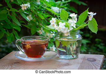 A cup of tea and a vase with sprigs of jasmine. Green blurred background. Blooming jasmine branches in the background. Summer mood. Bright summer sunny day.