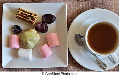 A cup of tea and various sweets