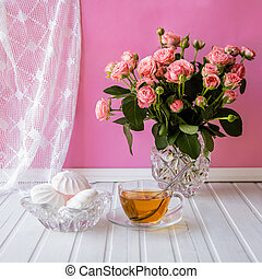 A cup of tea, candy and a bouquet of roses on a pink background