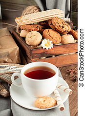 A cup of tea with biscuits tray around
