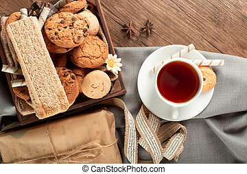 A cup of tea with biscuits tray around. Top view