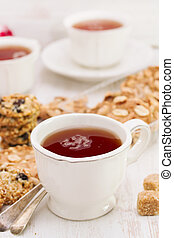 a cup of tea with healthy cookies on white wooden background