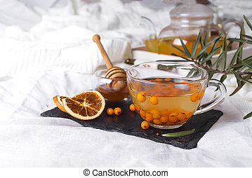A cup of tea with sea buckthorn and herbs on a stone tray with honey on the bed