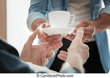 A cup of warm tea being in mans hands.