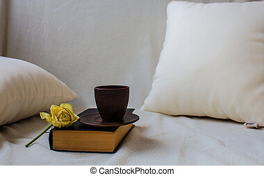 a cup on the book with rose
