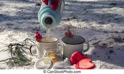 A cup with a hot drink in the winter forest.