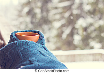 A cup with a hot drink on the background of the winter forest