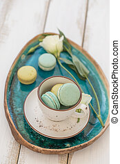 A cup with green macaroons