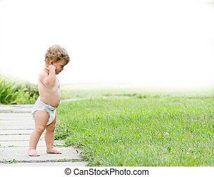 a curly baby in a diaper looks at the green grass