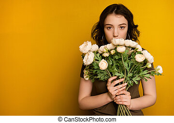 A curly dark-haired girl stands on a yellow background and looks at the camera from behind a bouquet of flowers.