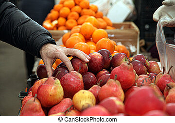A customer choosing red apples in the market