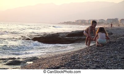 A cute and funny children runs on the water, the boy and girl are on the nature near a sea, strong wind and waves. they play with stones