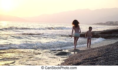A cute and funny children runs on the water, the boy and girl are on the nature near a sea, strong wind and waves. they dance and jump with waves