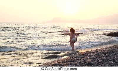 A cute and funny children runs on the water, the boy and girl are on the nature near a sea, strong wind and waves. they dance and jump with waves on sunset
