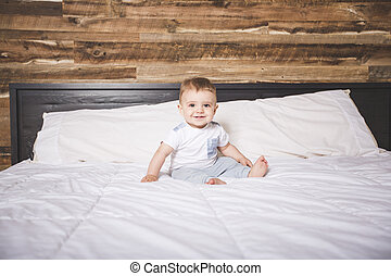 Cute Baby boy in white bedding.