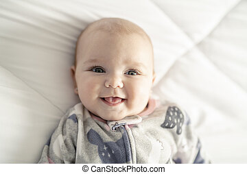 A Cute baby girl on a white bed at home