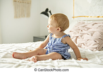 Cute baby girl on bed at home