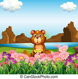 A cute bear near the flowers at the riverbank