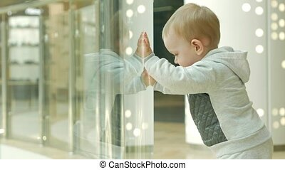 A cute blond boy of two years is considering a store through the glass. The kid carefully examines the inside of the shop