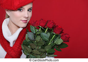 A cute blond holding a bunch of roses.