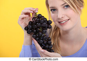 A cute blond holding grapes.
