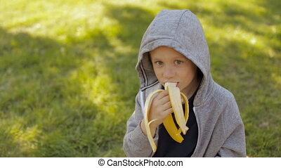 A cute boy eating a banana
