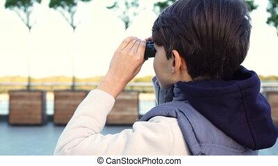 A cute boy examines the neighborhood through binoculars