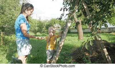 A cute boy with his mother near the cherry tree. A woman takes out stones and gives her son berries.