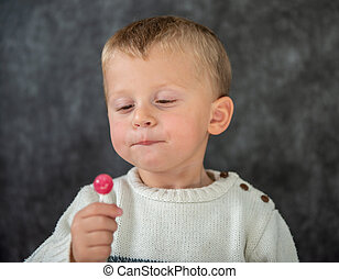 cute child is eating a lollipop