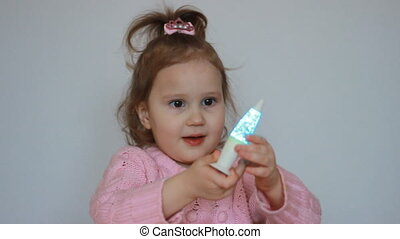 A cute child plays with a flashlight and looks at the...