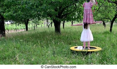 A cute girl dances in the natural garden. Little girl dances and jumps on a small trampoline. Little girl wears white wedding dress