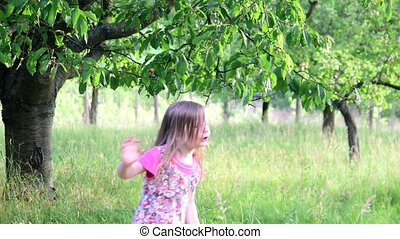 A cute girl dances in the natural garden. Little girl dances and jumps on a small trampoline. Little girl wears floral dress and white hat