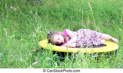 A cute girl dances in the natural garden. Little girl dances and jumps on a small trampoline. Little girl wears floral dress