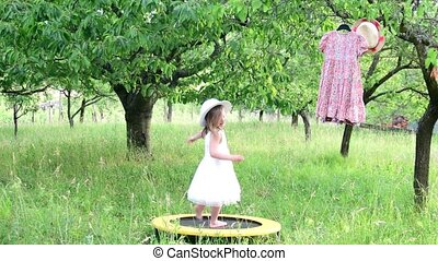 A cute girl dances in the natural garden. Little girl dances on a small trampoline. Little girl wears white wedding dress