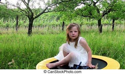 A cute girl has a rest in the nature garden. Little girl wears white wedding dress