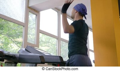 A cute guy runs on a treadmill in the gym. 4k, slow motion.