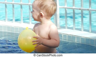 A cute kid plays in a children's pool with an inflatable yellow ball. He walks on the bottom with his feet.