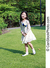 A cute little asian girl in playing happily in the garden