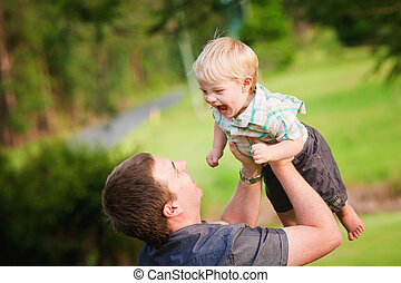 A cute little blond haired, blue eyed boy plays with his Dad in an outdoor field
