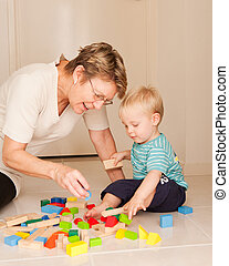 A cute little blong haired blue eyed boy plays with his Nanny, grandmother, au pair.