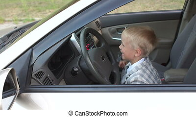 The child is having fun and playing behind the wheel in dad's car.