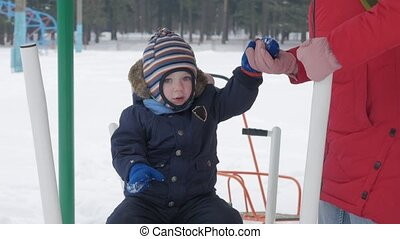 A cute little boy and a young mother are engaged in outdoor...