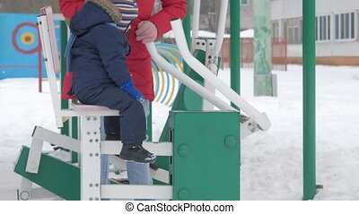A cute little boy and a young mother are engaged in outdoor exercise equipment. It's hard for a kid to reach the handles of equipment