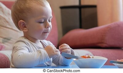 A cute little boy eats porridge with pieces of meat at a...