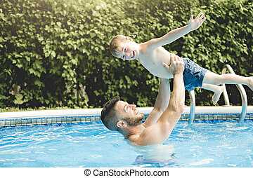 Cute little boy having fun with parents in pool