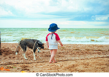 A cute little boy is walking along the beach with a dog
