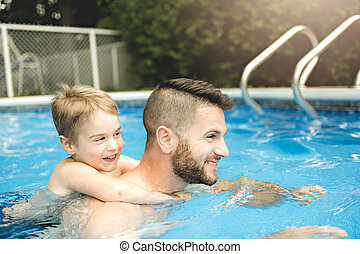 Cute little boy learning to swim with parents in pool