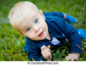 A cute little boy on the green grass in the outdoors.  He is making eye contact with the camera